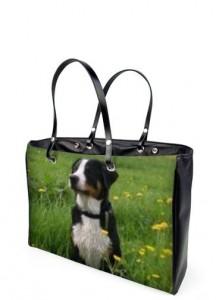 Eine schwarze Handtasche aus Vinxl mit einem Foto eines Hundes auf einer Wiese