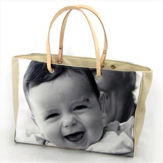 Eine Handtasche aus Leder in beige bedruckt mit einem Foto eines Babys in schwarz/weiss