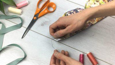 hand mit vernähtem stoffstück und fäden